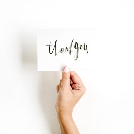 Composition pâle minimale avec la main de la jeune fille tenant la carte avec citation Merci écrit en style calligraphique sur papier sur fond blanc. Plat poser, vue de dessus