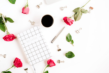background: Workspace with laptop, red roses flowers, coffee cup, notebook and clips on white background. Flat lay, top view. Feminine background.
