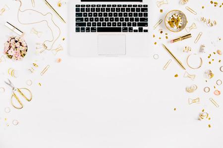 Fondo del blog de la belleza. Espacio de trabajo con portátil, accesorios femeninos de estilo dorado. Oro oropel, tijeras, pluma, anillos, collar, pulsera sobre fondo blanco. Flat lay, vista superior mesa de escritorio de oficina.