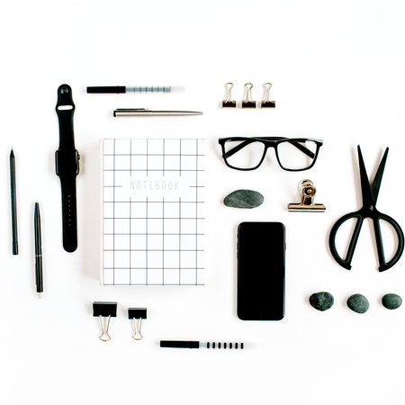 White office desk with supplies. mobile phone, glasses, notebook, scissors and office supplies on white background. Flat lay, top view office table desk.