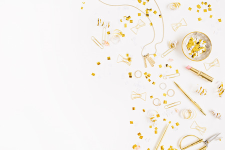 feminine background: Beauty blog background. Gold style feminine accessories. Golden tinsel, scissors, pen, rings, necklace, bracelet on white background. Flat lay, top view. Stock Photo