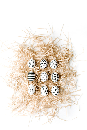Fancy Easter eggs in nest on white background. Flat lay, top view. Traditional spring concept. Zdjęcie Seryjne