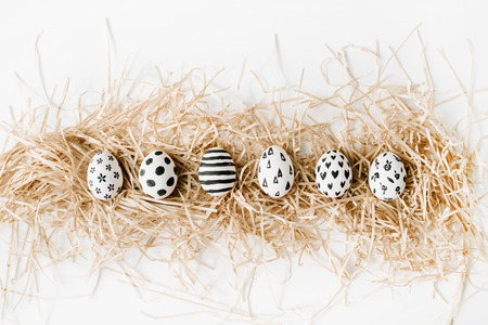 Fancy Easter eggs in nest on white background. Flat lay, top view. Traditional spring concept. Stock Photo