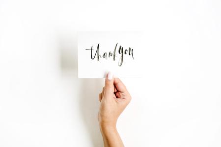 Composizione pallida minima con la mano della ragazza che tiene scheda con citazione Grazie scritto in stile calligrafico su carta su sfondo bianco. Vista piana, vista dall'alto Archivio Fotografico - 74022840
