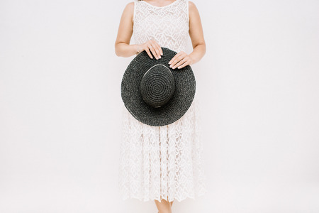 Young pretty woman in white dress holding black hat near white wall.