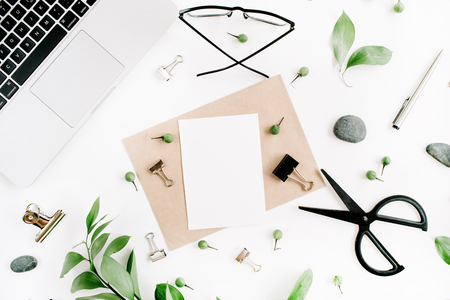 White office desk workspace with paper blank, green leaves and office supplies. Laptop, scissors, glasses on white background. Flat lay, top view, mockup. Zdjęcie Seryjne - 74745305