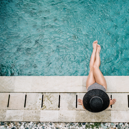 Young woman in hat relaxing near swimming pool. Top view Фото со стока