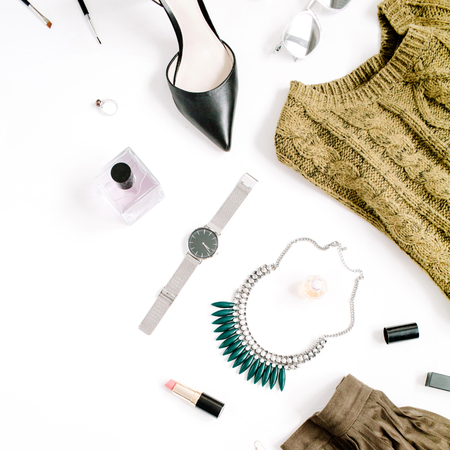 Beauty blog concept. Female clothes and accessories: green skirt and sweater, watches, necklace, lipstick, shoes, sunglasses on white background. Flat lay, top view trendy fashion feminine background.