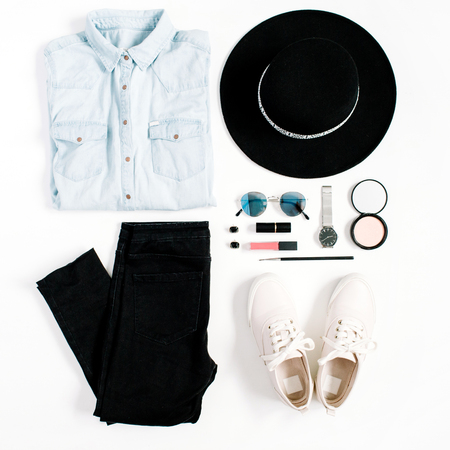 Beauty blog concept. Woman clothes and accessories: hat, jeans, t-shirt, watches, sunglasses, sneakers on white background. Flat lay, top view trendy fashion feminine background.