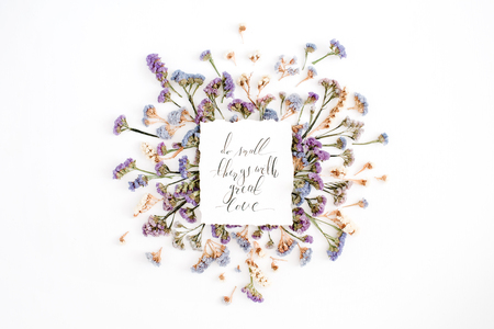 Inspirational quote Do small things with great love written in calligraphic style on paper with blue and purple dried flowers on white background. Flat lay, top view