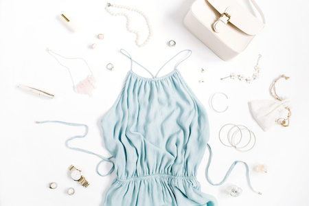 Beauty blog concept. Woman clothes and accessories: blue dress, purse, watches, bracelet, necklace, rings, lipstick on white background. Flat lay, top view trendy fashion feminine background. Banque d'images