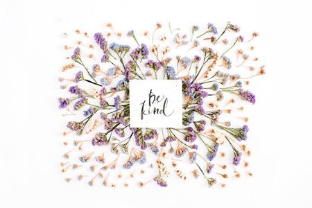 """Woorden """"Be Kind"""" geschreven in kalligrafische stijl op papier met blauwe en paarse gedroogde bloemen op witte achtergrond. Plat leggen, bovenaanzicht"""