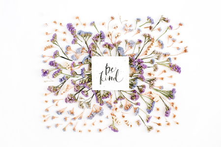 Words Be Kind written in calligraphic style on paper with blue and purple dried flowers on white background. Flat lay, top view
