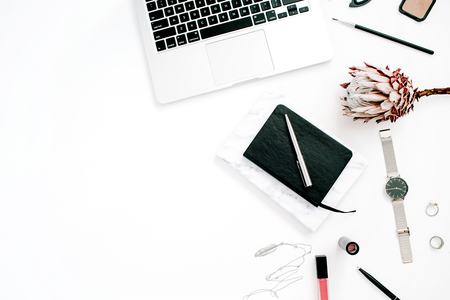 Blogger or freelancer workspace with laptop, protea flower, notebook and feminine accessories on white background. Flat lay, top view minimalistic decorated home office desk. Beauty blog concept. Banque d'images
