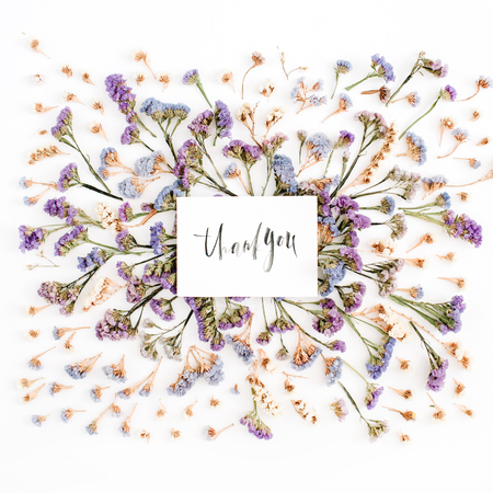 Words Thank you written in calligraphic style on paper with blue and purple dried flowers on white background. Flat lay, top view