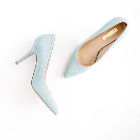 美容ブログのコンセプトです。白背景に淡いブルー女性靴。フラット横たわっていた、トップ ビュー流行のファッション フェミニンな背景。