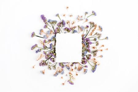 Leeres Weißbuchfreier raum auf blauem und purpurrotem getrocknetem Blumenrahmen auf weißem Hintergrund. Flachlegen, Draufsicht Standard-Bild - 76689720