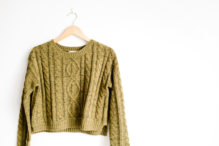 warm cloth: Front view of beauty trendy green female sweater on hanger near white background. Fashion concept. Stock Photo