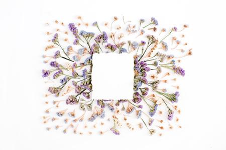 Leeres Weißbuchfreier raum auf blauem und purpurrotem getrocknetem Blumenrahmen auf weißem Hintergrund. Flachlegen, Draufsicht Standard-Bild - 76889937