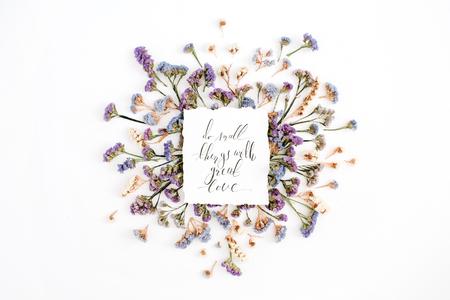"""Inspirerende citaat """"Doe kleine dingen met grote liefde"""" geschreven in kalligrafische stijl op papier met blauwe en paarse gedroogde bloemen op witte achtergrond. Plat leggen, bovenaanzicht Stockfoto"""