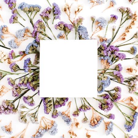 Leeres Weißbuchfreier raum auf blauem und purpurrotem getrocknetem Blumenrahmen auf weißem Hintergrund. Flachlegen, Draufsicht Standard-Bild - 77755704