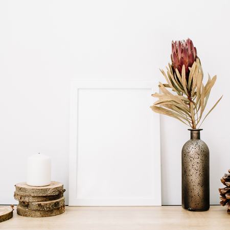 Front view blank mock up of photo frame with protea flower and trendy stuff at white background. Minimalistic decorated home office concept. Stock Photo