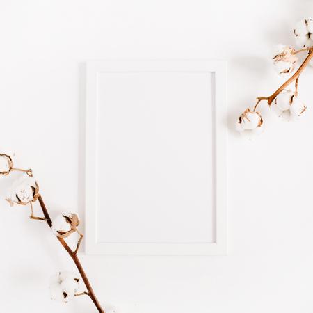 흰색 빈 사진 프레임 조롱 및 흰색 배경에 목화 분기. 평면 누워, 상위 뷰입니다. 스톡 콘텐츠