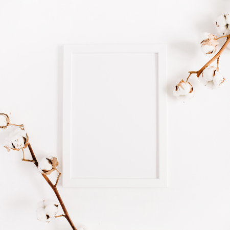 White blank photo frame mock up and cotton branches on white background. Flat lay, top view.