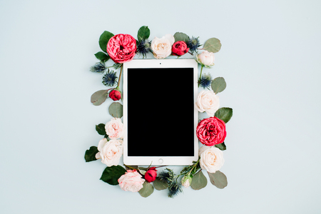beige: Flat lay floral frame with tablet, red and beige rose flower buds on pale pastel blue background. Top view decorated concept. Stock Photo