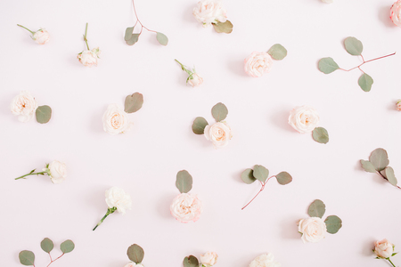 beige: Flowers pattern texture made of beige roses, eucalyptus branches on pale pastel pink background. Flat lay, top view. Valentines background. Floral texture background. Stock Photo