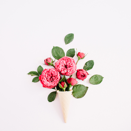 Waffle cone with red roses bouquet on pale pastel pink background. Flat lay, top view