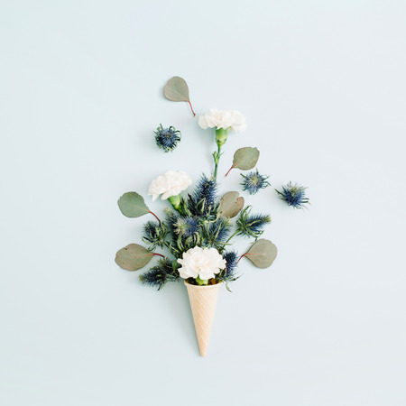 Waffle cone with white carnation and eucalyptus bouquet on pale pastel blue background. Flat lay, top view Zdjęcie Seryjne - 79077076