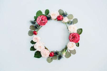 Couronne de fleur faite de roses beige et rouge, branches d'eucalyptus sur fond bleu pastel pâle. Plat poser, vue de dessus. Fond de texture florale. Banque d'images - 79077909
