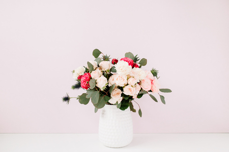 Beautiful flowers bouquet in flowerpot near pale pastel pink wall. Floral lifestyle composition.