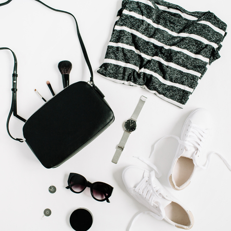 Trendy fashion black styled woman clothes and accessories collection on white background. Flat lay, top view. Sneakers, watches, sunglasses, t-shirt, purse.