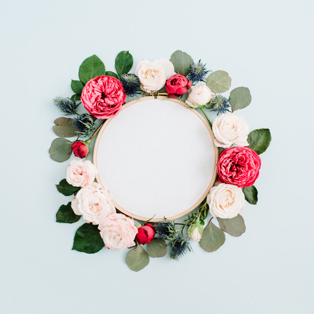 Embroidery frame with beige rose flower buds isolated on pale pastel blue background. Flat lay, top view decorated concept. Stock Photo
