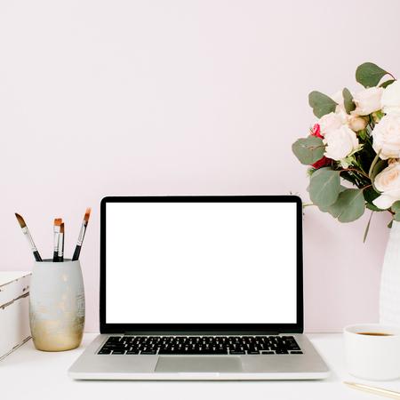 Het bureau van het huis met lege het schermlaptop, mooi rozen en eucalyptusboeket, witte uitstekende kist voor bleke pastelkleur roze achtergrond. Blog, website of sociale media-concept.