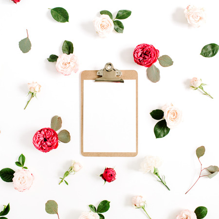 Flat lay floral frame with clipboard, red and beige rose flower buds pattern on white background. Top view decorated concept.