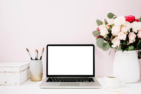 빈 화면 홈 사무실 책상 노트북, 아름 다운 장미 및 유칼립투스 꽃다발, 창백한 파스텔 핑크 배경 앞에 흰색 빈티지 관. 블로그, 웹 사이트 또는 소셜 미 스톡 콘텐츠
