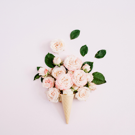 Waffle cone with pink bombastic roses bouquet on pale pastel pink background. Flat lay, top view