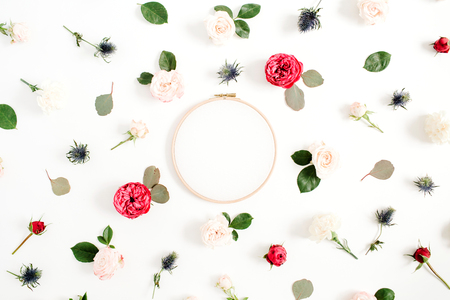 Embroidery frame with red and beige rose flower buds pattern on white background. Flat lay, top view decorated concept.