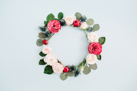 Bloemkaderkroon van beige en rode rozen, eucalyptustakken op bleke pastelkleur blauwe achtergrond wordt gemaakt die. Plat leggen, bovenaanzicht. Floral textuur achtergrond. Stockfoto