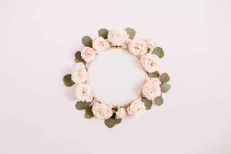 Embroidery frame with beige rose flower buds isolated on pale pastel pink background. Flat lay, top view decorated concept.