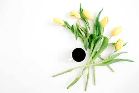 Cup of coffee and yellow tulip flowers on white background. Flat lay, top view.