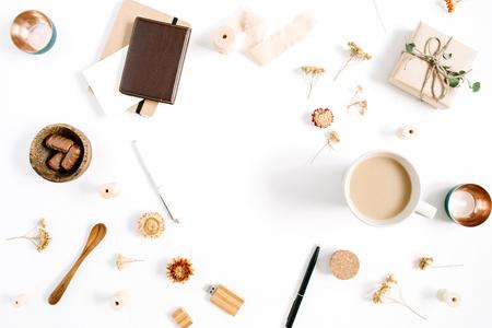 블로거 또는 프리랜서 작업 영역 커피 잔, 노트북, 과자 및 흰색 배경에 액세서리의 프레임. 평면 누워, 상위 뷰 최소한의 갈색 스타일 홈 사무실 책상.  스톡 콘텐츠