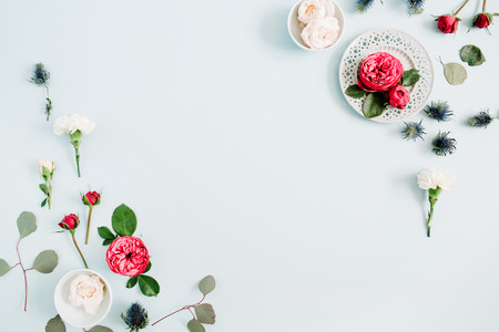 Flowers border frame made of red and beige roses, white carnation and eucalyptus branches on pale pastel blue background. Flat lay, top view. Floral texture background. Stock Photo