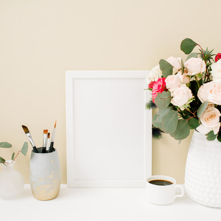 フォト フレーム モックアップ、美しいバラの花と淡いパステル ベージュの背景の前でユーカリ花束のホーム オフィス デスク。ブログ、ウェブサイ