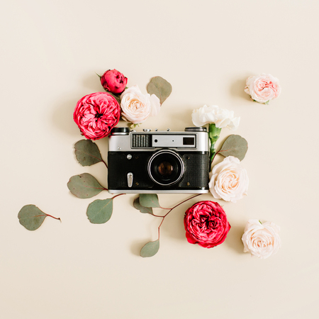 Vintage retro camera, red and beige rose flower buds pattern on pale pastel beige background. Flat lay, top view decorated concept.