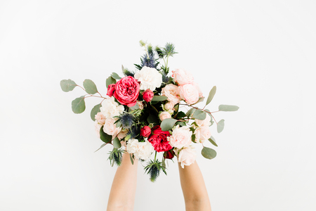 Girls hands holding beautiful flowers bouquet: bombastic roses, blue eringium, eucalyptus, isolated on white background. Flat lay, top view. Floral composition