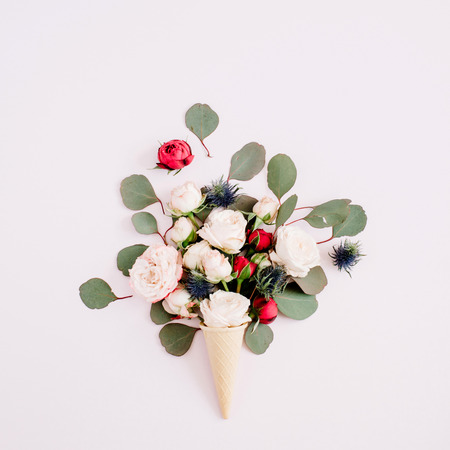 Waffle cone with red, beige roses and eucalyptus bouquet on pale pastel pink background. Flat lay, top view Фото со стока